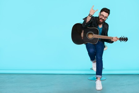 Happy young punk rocker with a guitar and dark sunglasses on blue background. Full body man in leather jacket showing Rock sign with copy space