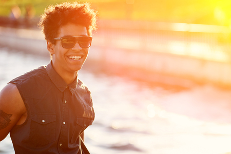 sunglight: Young African American man smiling on sunglight background. Afroamerican Student at lake on sunny day