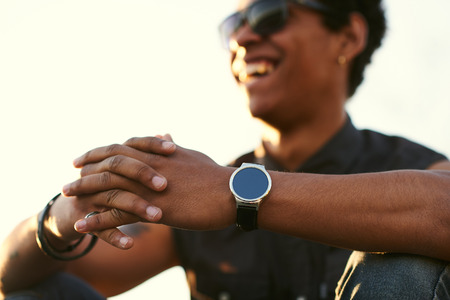 syncing: Man wearing round smartwatch. Black young man Closeup of hands and wrist with smart watch screen.