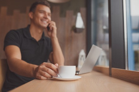 focus on the foreground: Focus on foreground. multitasking concept. man using tablet, laptop and cellphone while drinking a cup of coffee Stock Photo