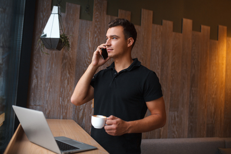mid adult: Mid adult business man standing and drinking a cup of coffee, looking out of window. Side view
