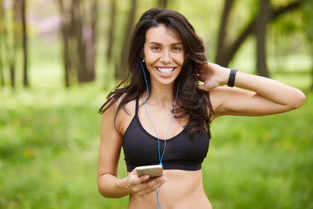 40 year old woman: Portrait of a young sporty woman holding her smart phone after jogging outdoors. Fitness female listens to music before run outside