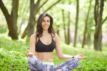 Young Female doing yoga meditation outdoor. Fit woman sitting in lotus pose in forest while smiling to camera