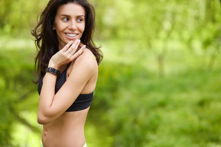 Female runner relaxing after run outdoor. Beautiful fit caucasian Fitness model with smart watch on her wrist looking to copy space outside on green blured background