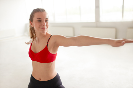 Portrait of young woman stretching her arms and looking away at gym. Beautiful girl performing yoga in warrior pose, Virabhadrasana.