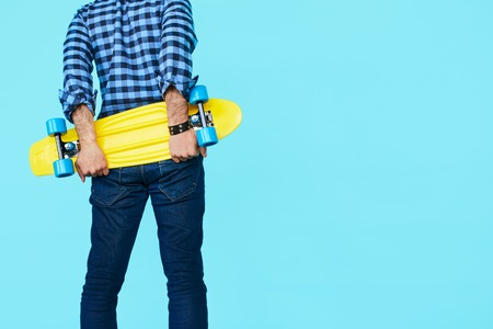 tenager: Closeup of Hipster holding his yellow penny skateboard with copyspace. Cool, Tenager back view