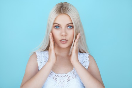 wide eyed: Wide eyed young teenage girl in shock over blue background. Fashion model with white hair surprised isolated on color background Stock Photo