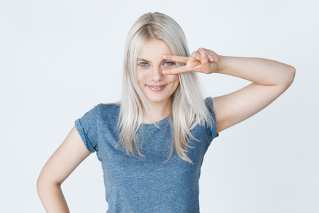 Natural makeup. White Hairstyle. Studio portrait of smiling blond girl over grey background showing peace sign. Two fingers symbol Imagens