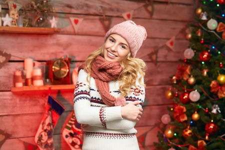 cosy: Lovely Happy Woman. Merry Christmas. Young female wearing warm clothes, cosy sweater, hat and scarf, smiling over christmas tree decorations.