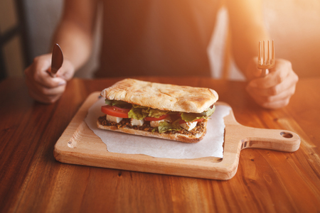 Big sandwich close up. Young man holding a fork and knife, eating healthy greek sandwich. Food at restaurant concept