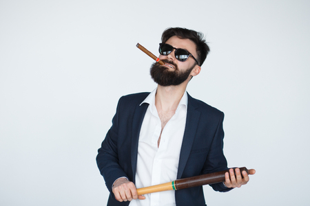 threatens: Portrait Of Young bearded man Holding Baseball Bat Over grey Background. Bad angry male smoking a cigar and threatens
