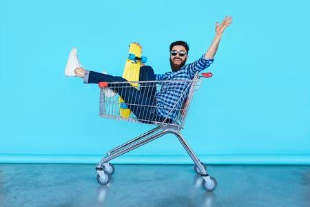 carro supermercado: apuesto hombre inconformista joven sentado en el carrito de la compra, mientras que sostiene un patín sobre el fondo de color azul turquesa