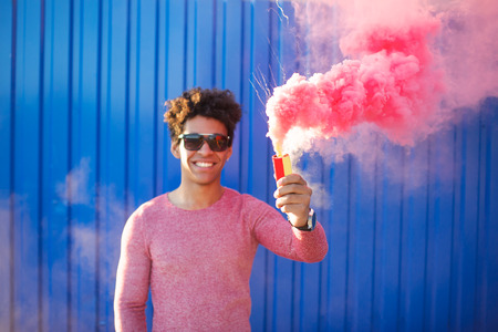 pyrotechnics: Focus on hand. pyrotechnics concept. Defocused happy cheerful man holding a smoke grenade over colorful background Stock Photo
