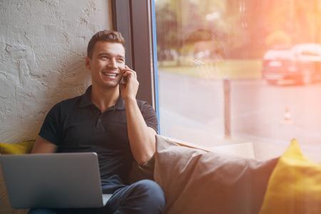 幸せな若い男が自宅のソファでノート パソコンと携帯電話を使用して。太陽フレアの効果を持つスマート フォンでハンサムな男性話して笑っていま