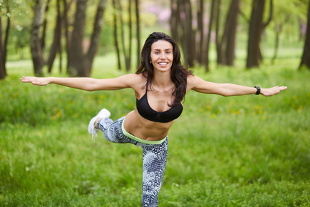 Sport fitness woman doing outdoor training workout. Mid age female balancing on one leg while smiling outside in park Stock Photo