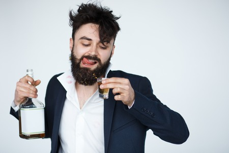 optional: Young man with beard is drunk. Bearded male in bad condition drinking whiskey. Funny alcoholic over white background
