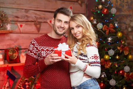 Portrait of happy smiling couple holding Christmas present. Holiday red wrapped gift box sharing over xmas decoration 版權商用圖片