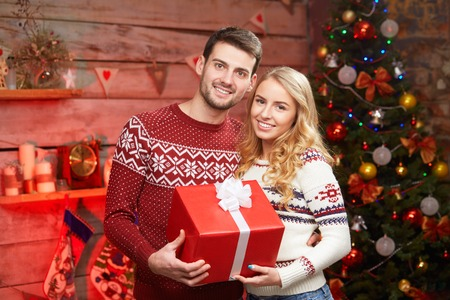 box size: Smiling young couple in fashion sweaters embracing and holding big size red gift box over christmas lights on background. Stock Photo