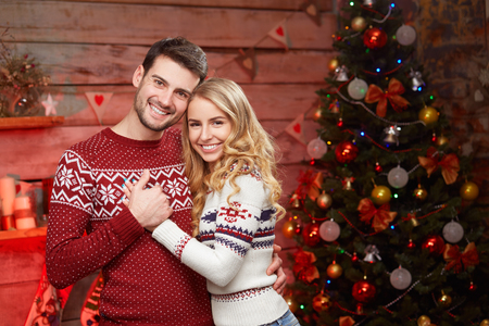 Sweet couple in winter sweaters hugging each other on christmas decorations background. Handsome man and blond young woman celebrating winter holidays 版權商用圖片