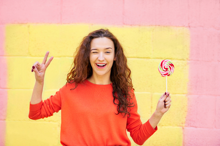 lolipop: Fashion portrait pretty woman in summer clothes showing peace and holding lolipop over colorful pink and yellow background