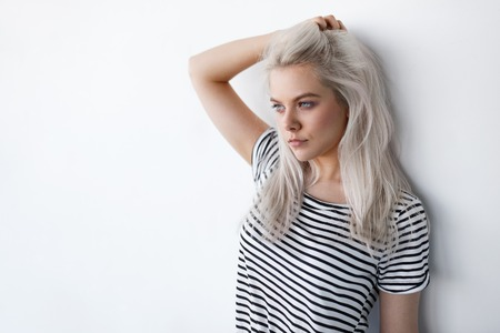 beautiful young blond woman posing while leaning on white wall with copy space. Hipster girl with blue eyes and bleached silver hair 스톡 콘텐츠