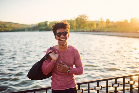 Portrait of young man smiling outside. Happy black african person with sport bag returning from training at sunset outdoors