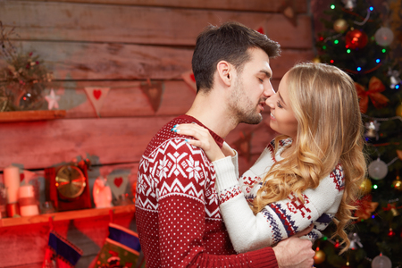 pullovers: Happy Young Couple by christmas tree kissing. two persons wearing knitted pullovers in love