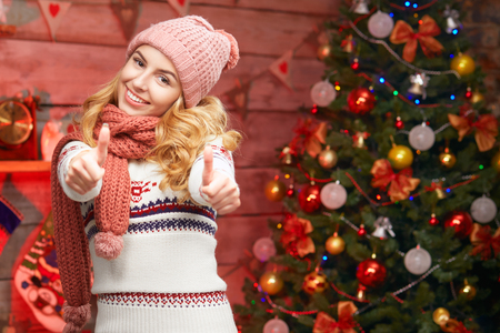 posing  agree: happy young woman in winter clothes showing thumbs up. Christmas concept. Smiling blond girl wearing sweater, scarf and hat Stock Photo