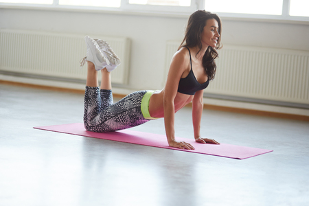 Beautiful woman in sportswear stretching on yoga mat in loft studio