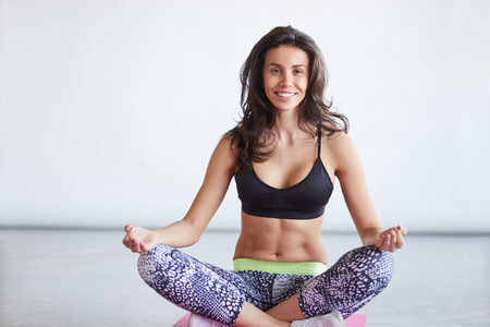 keeping fit: mature women keeping fit by doing yoga in studio. Female sitting in lotus position and smiling Stock Photo