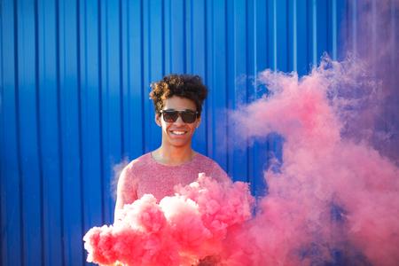 Homem americano africano jovem segurando uma granada de fumaça. Retrato colorido de moderno adolescente com fumaça vermelha sobre fundo azul. Banco de Imagens