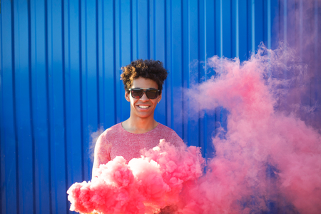 African American young man holding a smoke grenade. Colorful portrait of teenager hipster with red smoke on blue background. Foto de archivo