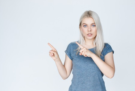 Giovane donna bionda con gli occhi azzurri che punta al lato isolato su uno sfondo bianco con copia spazio