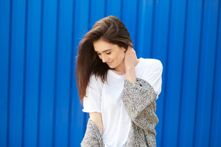 shy girl: beautiful shy girl smiling on a blue background. Young woman over blue wall Stock Photo