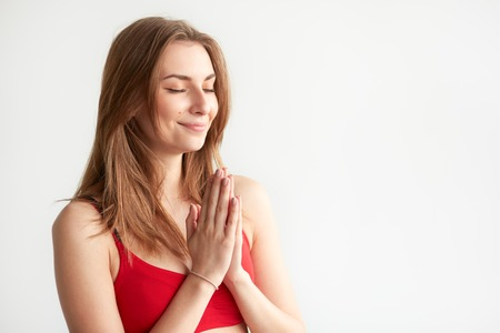 Beautiful Caucasian woman praying or practising yoga on white background with copyspace. Happy girl holding hands in namaste and keeping eyes closed