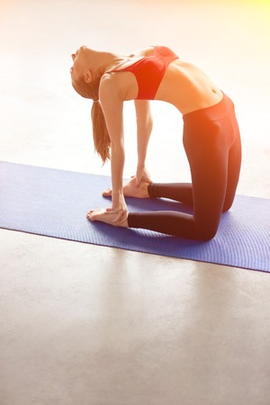 ushtrasana: Sporty beautiful young woman practicing yoga, doing Ushtrasana, Camel Pose, working out in studio, full length with lens flare filter effect