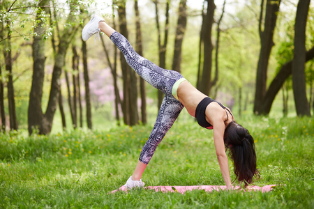 Woman practicing yoga outdoors in park, bending forward and lifting her leg up while facing down