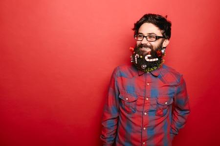 背景が赤い色の領域をコピーするのには装飾が施されたクリスマスひげ側にいるとこっけいな流行に敏感な男 写真素材