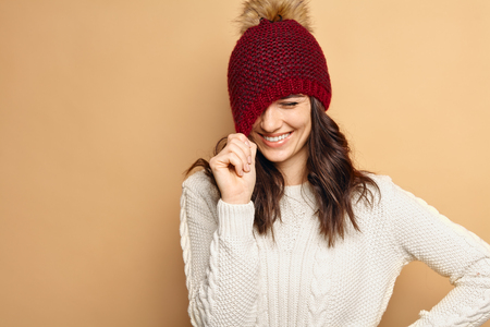 pulling beautiful: Beautiful natural looking young smiling brunette woman, wearing knitted sweater and stylish hat. Shy girl pulling her hat and laughing Stock Photo