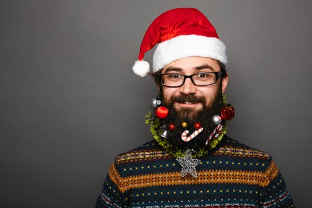 Close up portrait of bearded man with mustache and decorated beard as christmas tree on grey wall background with copy space. Programmer geek celebrating winter holidays