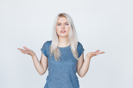 young blond woman with arms out shrugs shoulders. Hard choice over white background