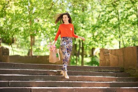 bajando escaleras: Retrato de moda chica de compras. Belleza de la mujer con el bolso de compras ir a casa del centro de renunciar en las escaleras al aire libre