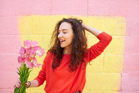 received: Happy emotional woman holding flowers over colorful yellow and pink background. Girl received gift