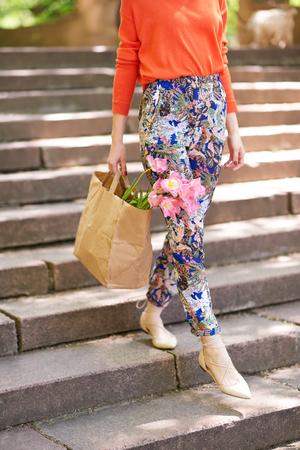 down the stairs: Primer plano de la niña de la celebración bolsa de papel con flores de primavera mientras se camina por las escaleras. concepto de compras al aire libre colorido