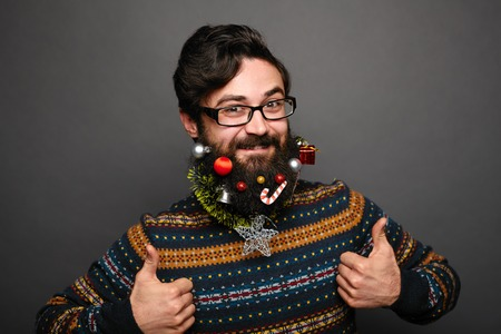 Portrait of caucasian man with big beard in knitted christmas sweater. Hipster male shows thumbs up. Stock Photo