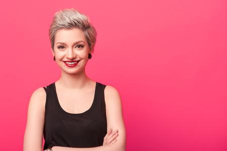 流行に敏感な女性のピンクの背景に笑みを浮かべて 写真素材