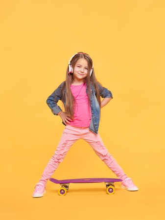 Pretty little girl standing on yellow background Banco de Imagens - 70273252