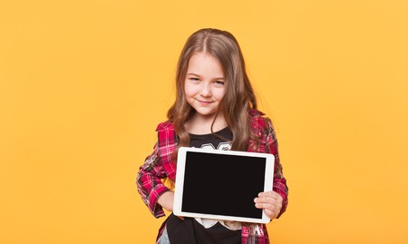 blank tablet: little girl showing blank black tablet pc on yellow background