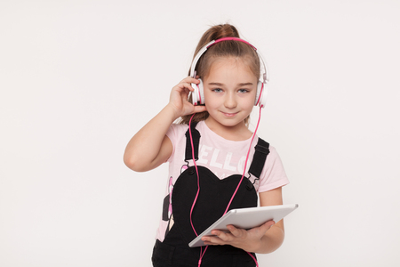 audio book: Portrait of little girl with tablet listening to audio book
