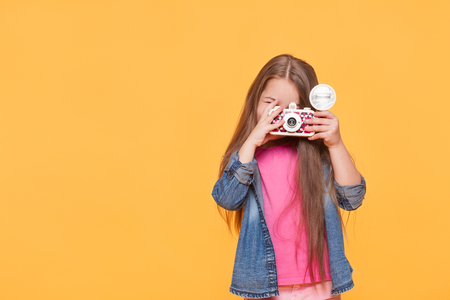 small child girl holding retro camera and taking photo over yellow color background with copyspace Stock Photo